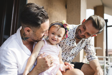 Happy gay couple with daughter at home