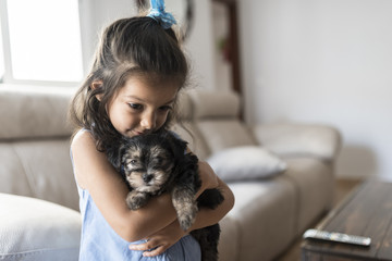 Little girl with her puppy at home
