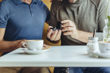 Close-up of gay couple with wedding ring in cafe