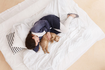 young girl in a blue pajamase sleeps on a bed with a red cat. Healthy day sleep. Top view