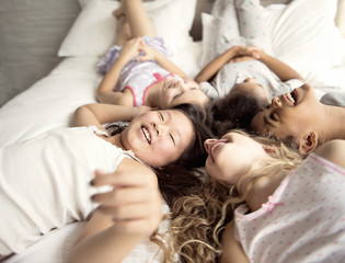large group of her friends taking goog time on bed
