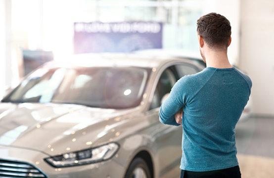 Young man looking at the new car