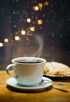 Hot Coffee with Pastry by Rainy Window