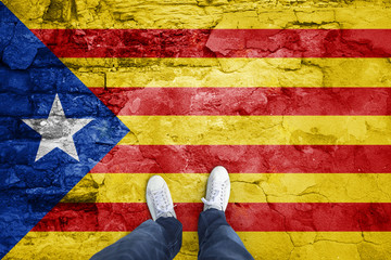 Point of view of a man standing on cracked cement floor with cracked Catalonian flag.