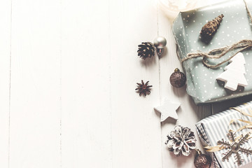 modern christmas flat lay. wrapped presents with ornaments and pine cones anise on rustic white wooden background top view, space for text. stylish gifts. seasonal greetings. happy holidays