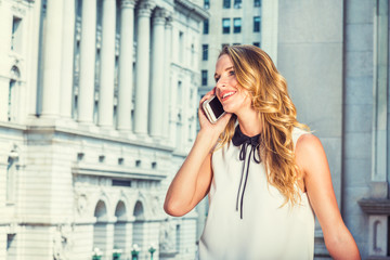 American Business Woman working in New York. Wearing sleeveless white dress, college student with blonde hair standing in front of vintage office building on street, talking on cell phone, smiling..