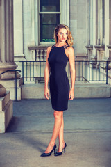 American Businesswoman Fashion in New York. Wearing sleeveless black dress, high heels, a pretty lady with long curly blonde hair standing in vintage style office building. Instagram filtered effect..
