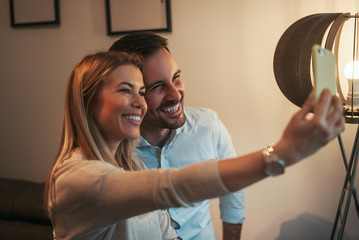 Young couple taking selfie in modern apartment.