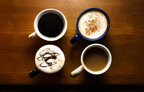 Four Varieties of Coffee in Mugs on Wooden Table
