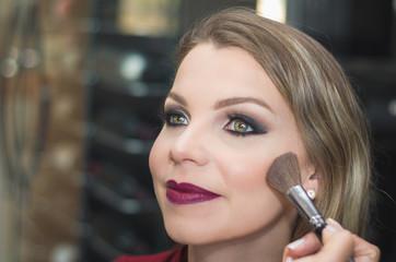 Ótimo conceito de maquiagem, maquiadora maquiando jovem mulher loira