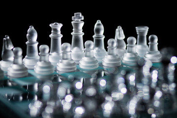 Glass Chess Board with Pieces Set Up And Ready for a Game Against a Dark Black Background