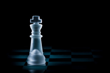 Glass King Chess Piece Stands Alone on Chessboard with Dark Background