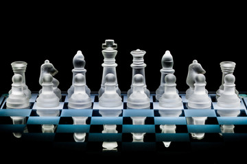 Glass Chess Set Standing on a Chessboard with a Dark Background, including the Rook, Knight, Bishop, Queen and King Pieces