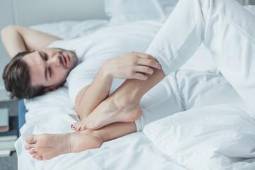 man touching leg of girlfriend in bed