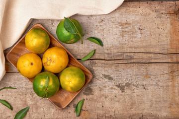 Tangerines. Fresh mandarin fruit with leaves on wooden background.