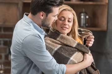 man covering girlfriend in plaid