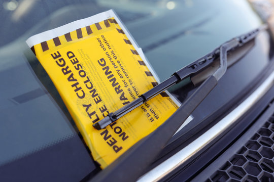 Penalty charge notice parking fine attached to windscreen