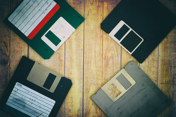 Old diskettes on a wooden pallet background