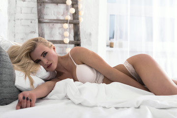 Attractive young blonde women in white underwear lies in the bed at morning.