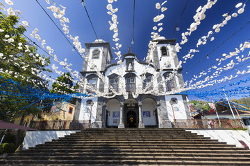 Blue and White decorative flowers strung up at the Church of Lady of Monte in the summertime in Funchal, Portugal.