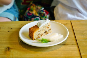 Slice of vegan apple cake with coconut whipped cream