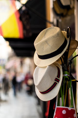 Two hats hanging on a stand in the middle of the street in Seville, Spain