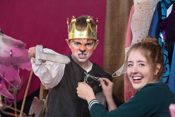 Child actor dressed as king wearing crown