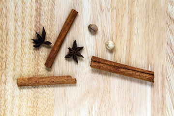 Top view of cinnamon stick with star anise spices and dried ginger on wooden desk