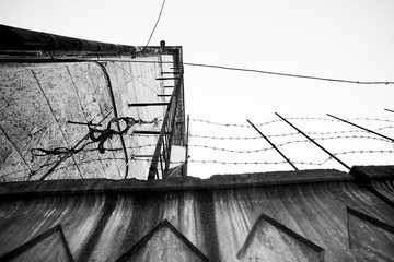 Industrial building with barbed wire from below, black and white photo