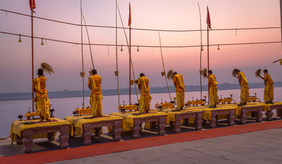 Ganga aarti ceremony ritual performed by priests at the Ganges river bank Varanasi India at dawn.
