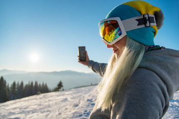 Woman snowboarder enjoying sunset after snowboarding, using her smart phone, taking pictures of winter nature in the mountains at winter ski resort Bukovel