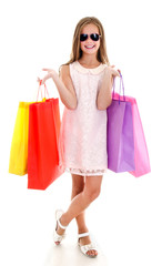Adorable little girl child in sunglasses holding shopping colorful paper bags