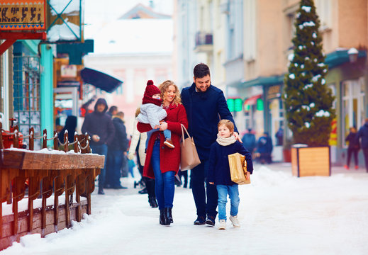 happy family walking together at snowy city street during winter holidays