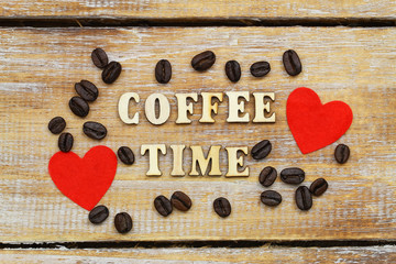 Coffee time written with wooden letters on rustic surface, two red hearts and coffee beans