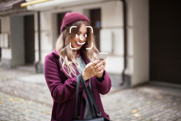 Face detection and unlocking of a mobile phone. A young girl is walking on the street. Face ID