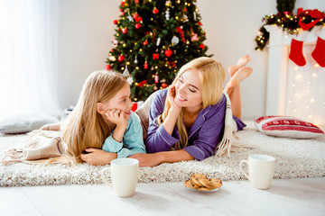 Cute mom with small little lovely girl bonding covered with cozy plaid lying down on carpet, in decorated room, stockings, pillow, in sleep wear barefoot, near fir tree. Maternity, friends, childhood