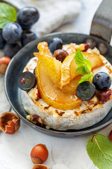 Skillet with baked camembert,caramelized pears and grapes.