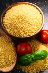 Bowl of uncooked couscous on wooden table