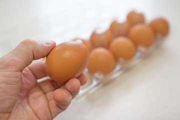Chicken egg in man's hand and eggs in box on background.