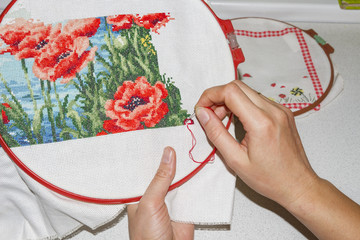 girl is embroidering picture close up. Hands, needle, thread and embroidery. Hobby house with own hands. Hand-made products.
