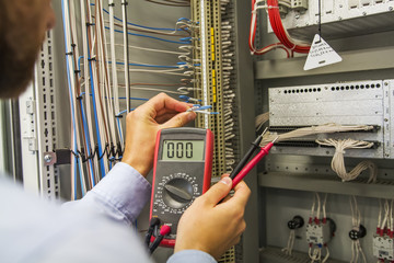 Electrician engineer with multimeter tests electrical control panel of automation equipment. Specialist in the Controller cabinet.