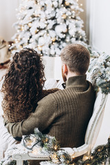 Man and woman reading a book together on the Christmas tree background. Christmas and New Year concept