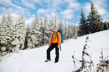 Hiker in winter mountains. Young man has a rest in mountains