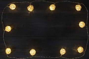 christmas garland lights on black background with copy space for your text. Top view