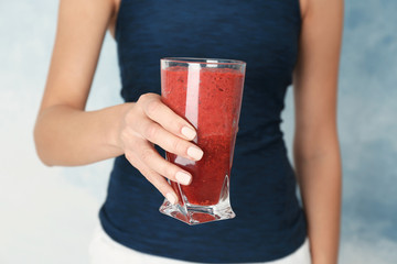 Woman holding glass with red smoothie on light background