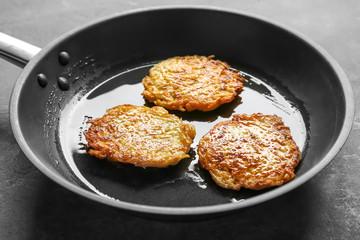 Frying pan with Hanukkah potato pancakes on table