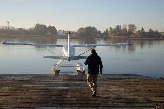 Young man aviator  walk dock water plane aviation