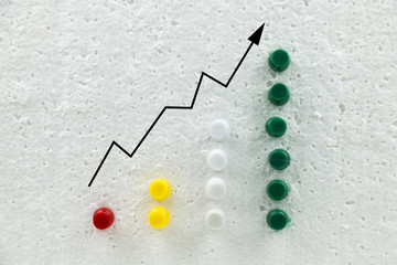 Colorful pins on polystyrene business growth chart.