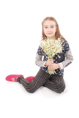 Portrait of a happy pretty girl holds a flower of a lily of the valley.