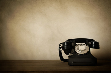 Vintage Black Telephone with Aged Effects on Wooden Desk